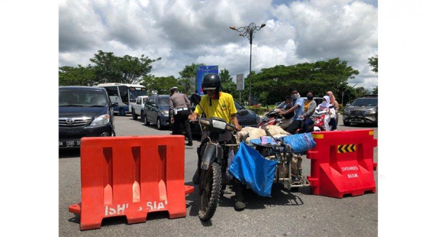 seorang-pengendara-becak-motor-melewati-penyekatan-arus-kendaraan-di-bundaran-mempura.jpg