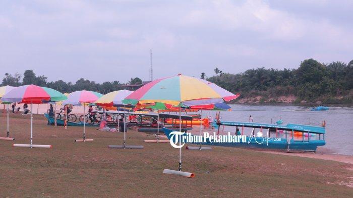Payung dan Karpet di Kawasan Pulau Cinta Teluk Jering disewakan untuk para pengunjung,  Sabtu (27/2/2021)