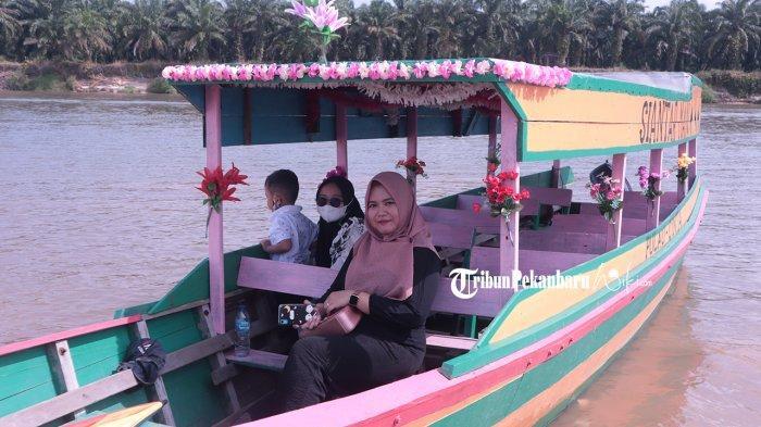 Pengunjung menaiki perahu hias di kawasan Pulau Cinta Teluk Jering