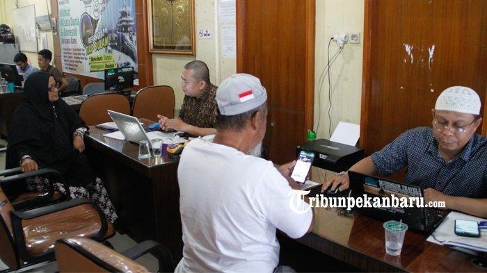 Petugas travel Muhibbah yang berada di Jalan Kartini Pekanbaru sedang melayani calon jemaah umroh, Kamis (27/2/2020)