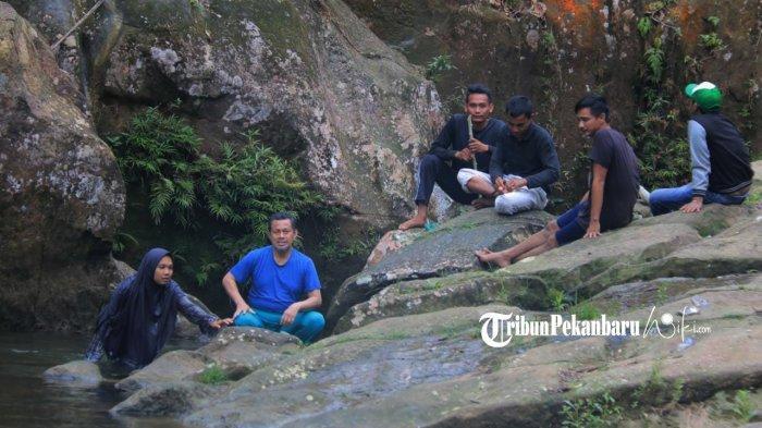 Pjs Bupati Rokan Hulu Masrul Kasmy saat menikmati keindahan alam wisata Batu gajah saat libur panjang cuti bersama lalu