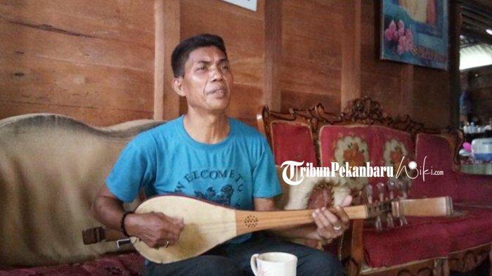 Zainudin, warga Kampung Zapin Desa Meskom tengah asyik memainkan alat musik gambus kala tribunpekanbaruwiki.com berkunjung