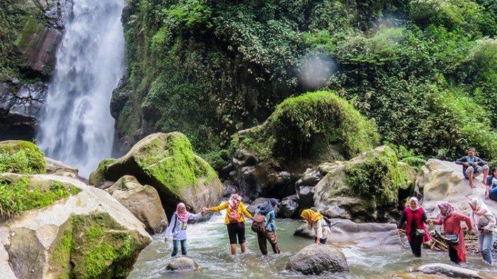 Pengunjung menyeberangi sungai menuju Air Terjun Kedung Kayang.