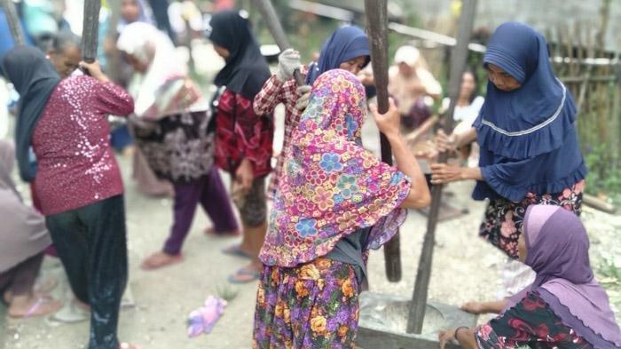 Kelompok KPM PKH Mulia Desa Mulia Kecamatan Teluk Keramat sedang menumbuk amping.