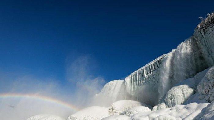 Pemandangan air yang mengalir di antara es yang membeku di Air Terjun Niagara yang terlihat dari bawah air terjun, New York, Amerika Serikat (dok. REUTERS/Lindsay DeDario)