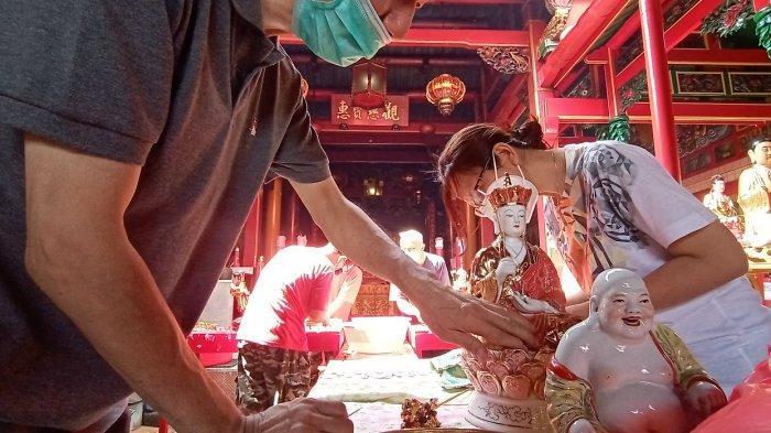 Seorang pengurus menyikat patung menggunakan air sabun di Klenteng Tien Kok Sie, Minggu (31/1/2021).