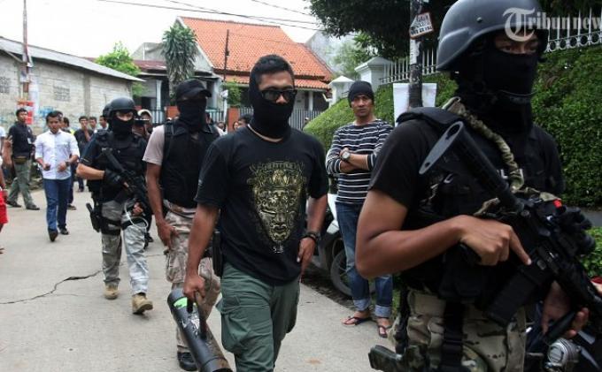 Polisi usai melakukan penggeledahan di kawasan Delima Setu, Rempoa, Ciputat, Tangerang Selatan, Rabu (1/1/2014). Densus 88 Antiteror Polri sebelumnya melakukan penyergapan dan menembak mati 6 orang terduga teroris di Ciputat.