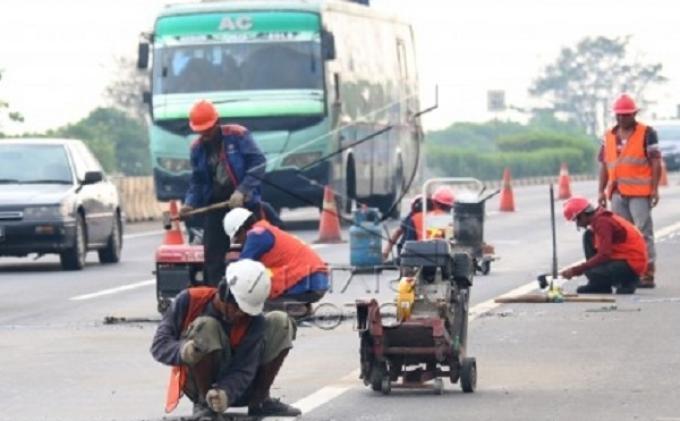 Sejumlah pekerja tengah melakukan perbaikan di KM 51 Jalan Tol Tangerang Merak, Tangerang, Banten, beberapa waktu lalu. Kini jalan tol tersebut diklaim siap digunakan untuk arus mudik Lebaran 2014.