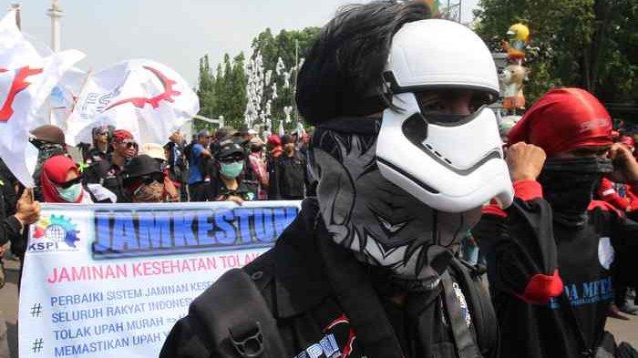 Massa buruh berunjuk rasa dalam rangka memperingati Hari Upah Kerja Layak Sedunia di depan Istana Negara, Jalan Medan Merdeka Utara, Jakarta Pusat, Sabtu (7/10).