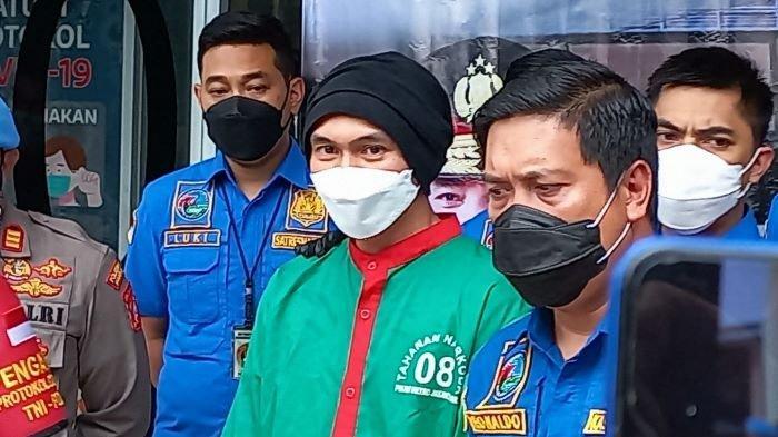 Anji Manji saat dihadirkan polisi didepan wartawan, Rabu (16/6/2021). Anji Manji terlihat memakai baju tahanan hijau. Kedua tangan Anji Manji di borgol. Anji Manji tetap memakai masker dan berpenutup kepala hitam.