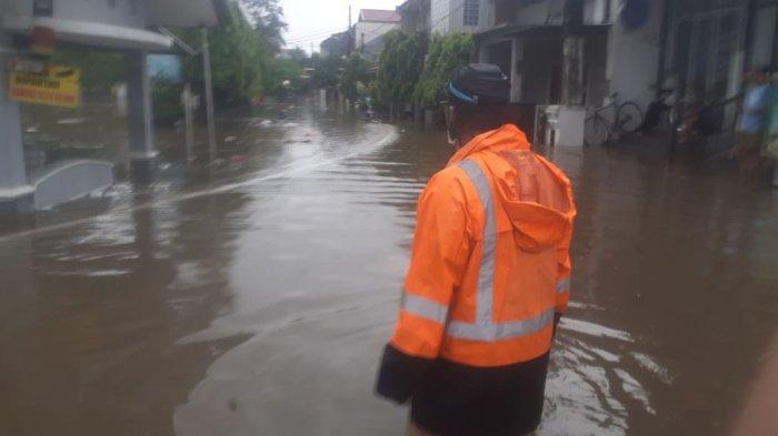 Petugas mengatami banjir di Perumahan Sarigaperi di Jatibening 1, Pondok Gede, Kota Bekasi.