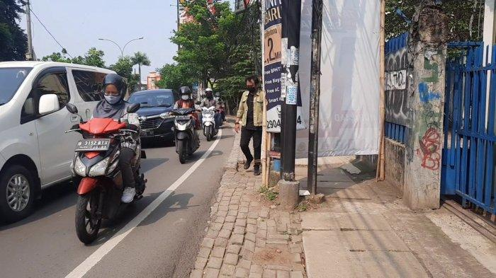 Pejalan kaki sedang melintas di pinggir trotoar karena akses terhalang baliho Muhamad - Saraswati saat keadaan lalu lintas di Jalan Ir H Juanda, Cirendeu, Ciputat Timur, Kota Tangsel.