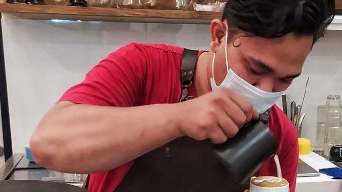 Barista Omana Coffee Bintaro sedang membuat latte art pesanan pelanggan yang datang.