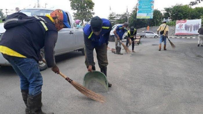 Sejumlah petugas Dinas Pekerjaan Umum membersihkan pasir dan kerikil di Jalan Ciater Raya, Serpong, Jumat (11/12/2020).