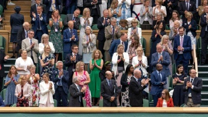 Dame Sarah Gilbert, kanan bawah, bertepuk tangan di Wimbledon