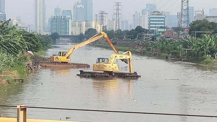 Dua alat berat sedang mengetuk endapan lumpur dan sampah di Kali Banjir Kanal Barat di kawasan Kampung Bakti, Cideng, Jakarta Pusat, Selasa (20/10/2020).
