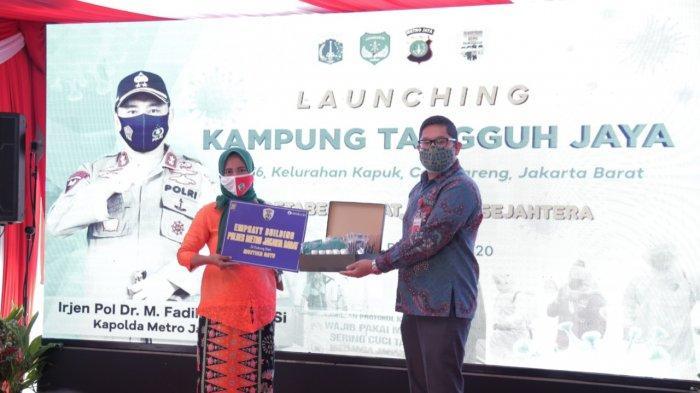 Chief Financial Officer PT Mustika Ratu (tbk), Jodi Andrea Suryokusumo, menyerahkan bantuan secara simbolis 1000 stater pack jamu suplemen Herbamuno+, hand gel dan masker kepada warga Kampung Tangguh Jaya .