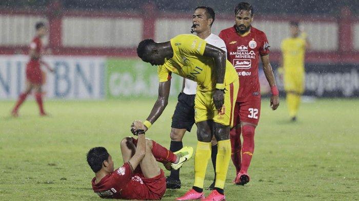 Setelah melakukan pelanggaran, striker BFC Ezechiel N'Douassel secara sportif membantu Evan Dimas untuk bangun