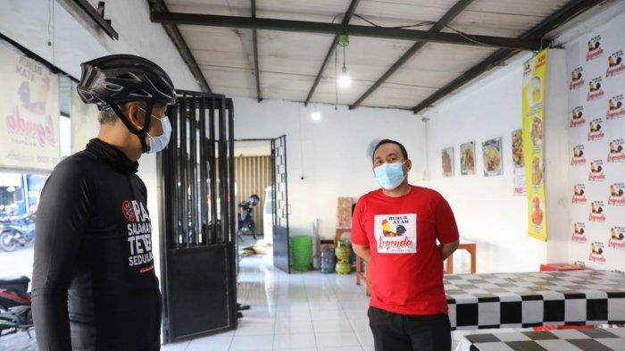 Gubernur Jawa Tengah Ganjar Pranowo berdialog dengan Romeo Julianto Sirait saat mampir ke warung Bubur Ayam Legenda di Jalan Brigjen Sudiarto (Jalan Majapahit) Kota Semarang, Senin (26/7/2021) pagi.