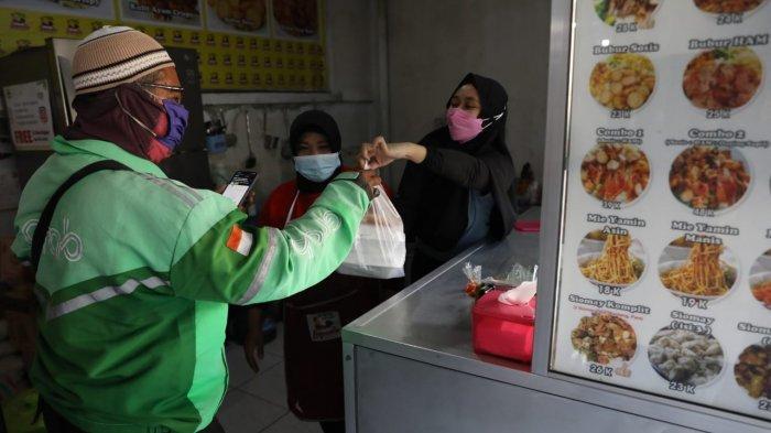 Pengemudi ojek online mengambil pesanan di warung Bubur Ayam Legenda di Jalan Brigjen Sudiarto (Jalan Majapahit) Kota Semarang, Senin (26/7/2021).