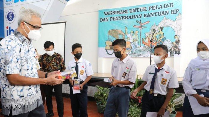 Gubernur Jawa Tengah Ganjar Pranowo menyerahkan secara simbolis, hadiah handphone bagi pelajar yang mengikuti vaksinasi di SMA 3 Surakarta, Rabu (4/8/2021).