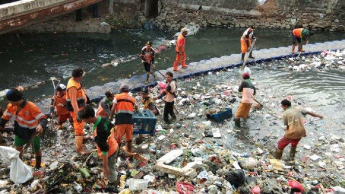 Petugas melakukan aksi gerebek sampah dalam upaya antisipasi banjir di Kali Cipinang, Minggu (18/11/2018).