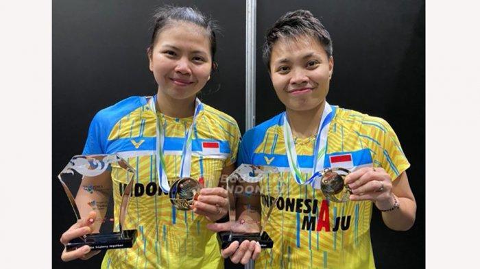 Greysia/Apriyani tersenyum dengan medali dan trophy juara Thailand Open