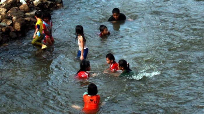 Berita Foto Sejumlah Anak Manfaatkan Kali Ciliwung yang Dangkal untuk Berenang