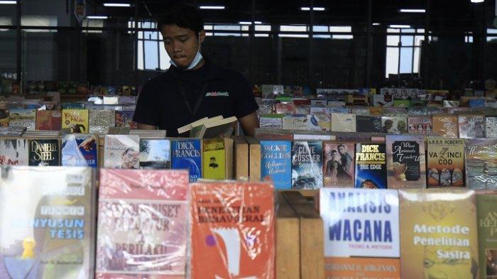 Karyawan menata buku di Gerai JakBook