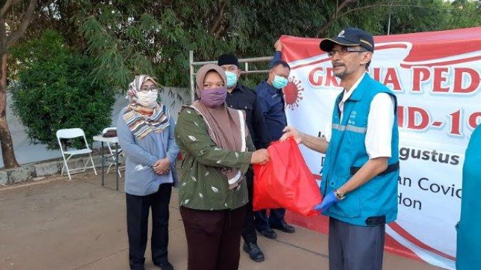 Koordinator RLC Kota Tangsel, Suhara Manullang sedang membagikan bantuan berupa paket sembako kepada warga sekitar RLC Kota Tangsel dan pedagang di Kantin Tandon Ciater.
