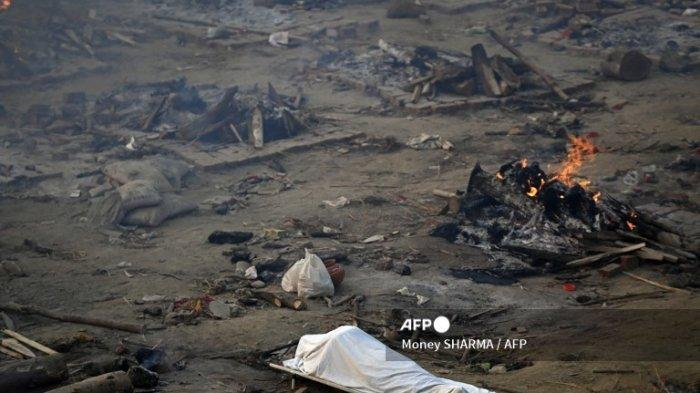 Sebuah mayat terbaring di tengah pembakaran kayu bakar para korban yang kehilangan nyawa karena virus Corona Covid-19 di tempat kremasi di New Delhi pada 26 April 2021.