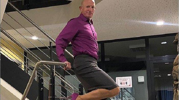 Mark Bryan mengenakan kemeja ungu pria yang berwarna senada dengan sepatu hak tinggi yang dikenakannya. Dia memadukannya dengna rok pendek.