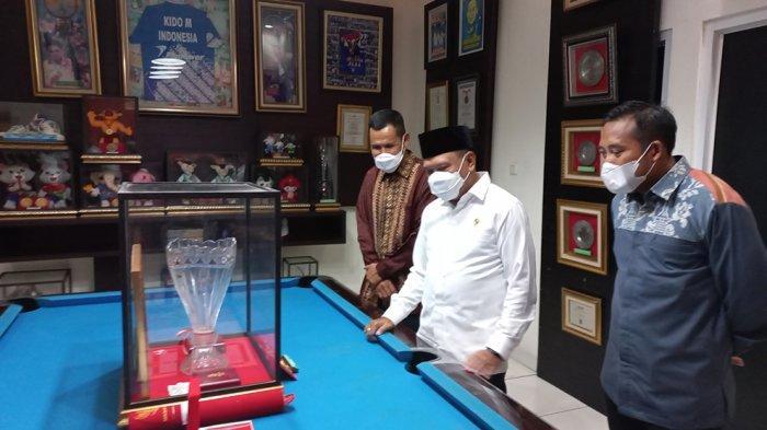 Menpora Zainudin Amali sedang melihat medali, trophy dan piagam penghargaan yang diraih oleh Markis Kido selama menjadi pebulutangkis nasional dan mengharumkan nama Indonesia di dunia internasional