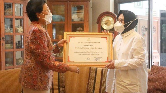 """Menteri Sosial Tri Rismaharini memberikan penghargaan """"Sentra Kreasi Award: Penghormatan Perlindungan dan Pemenuhan Hak-Hak Disabilitas"""" saat berkunjung ke kediaman mantan Mensos Intan Soeweno di kawasan Patra Kuningan, Jakarta Selatan, Kamis (17/6/2021)."""