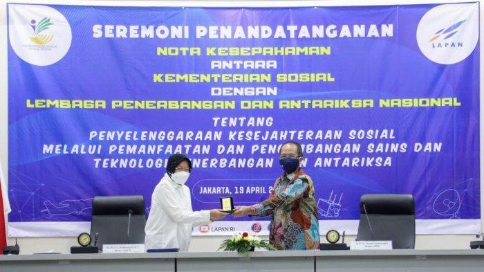 Menteri Sosial, Tri Rismaharini dan Kepala LAPAN, Thomas Djamaludin bertukar cinderamatan usai penandatanganan kerja sama di kantor LAPAN, Rawamangun, Jakarta Timur, Senin (19/4/2021).