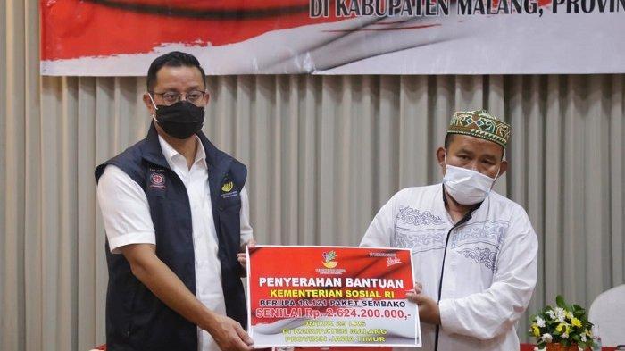 Menteri Sosial Juliari P. Batubara menyerahkan bantuan secara simbolik kepada perwakilan penerima bantuan paket sembako.