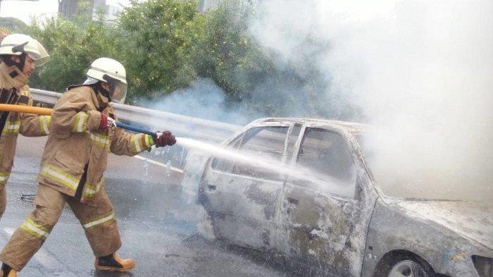 Petugas memadamkan sebuah mobil sedan yang terbakar di jalan tol Jagorawi.