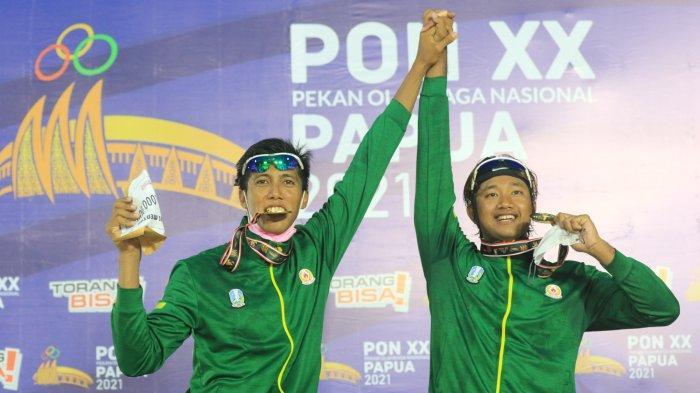 Pasangan voli pantai putra Jawa Timur 1, Mohammad Ashafiya/Rendy Verdian Licardo meraih medali emas dan merayakan kemenangan diatas podium