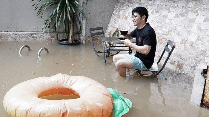 Rumah bintang sinetron dan chef Nicky Tirta di kawasan Kemang, Mampang Prapatan, Jakarta Selatan, ikut didatangi banjir, Sabtu (19/2/2021). Nicky Tirta tampak santai sambil minum kopi saat banjir mendatangi rumahnya.
