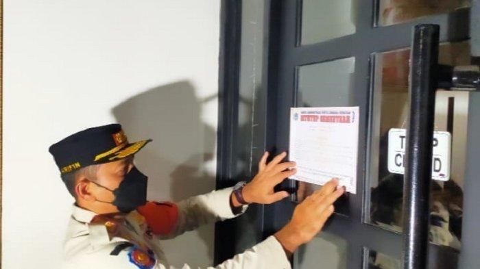 Kepala Satpol PP DKI Jakarta Arifin memasang stiker segel di Odin Cafe, Jalan Senopati, Kebayoran Baru, Jakarta Selatan, Sabtu (23/1/2021) dini hari. Kafe itu melanggar protokol kesehatan karena beroperasi sampai pukul 23.00 WIB, sedangkan batas waktu pukul operasional 19.00 WIB.