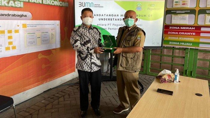 Senior Vice Presiden PT Pegadaian (Persero) Kanwil VIII Jakarta 1, Mulyono bertukar cinderamata dengan Wali Kota Bekasi DR. H. Rahmat Effendi usai menandatangani nota kesepahaman, di GOR Patrio Chandrabhaga, Senin (26/7/2021).