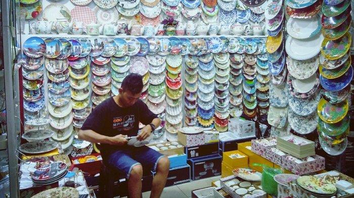 Pegawai Pelangi Keramik di Pasar Mayestik, Kebayoran Baru, Jakarta Selatan saat sedang memasang kawat pada piring gantung, Sabtu (27/1/2018)