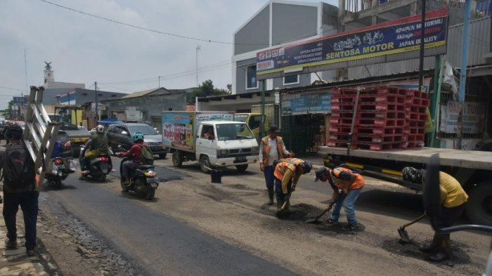 Petugas tengah melakukan perbaikan Jalan Cikarang-Cibarusah, Kabupaten Bekasi, pada Senin (15/2/2021).