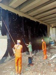 Petugas Penanganan Prasarana dan Sarana Umum (PPSU) Kelurahan Gelora, Kecamatan Tanah Abang Jakarta Pusat membersihkan bekas aksi vandalisme di jembatan layang Pejompongan.