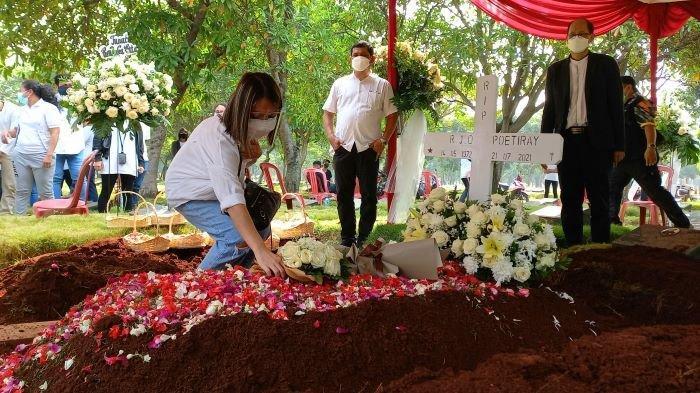 Penyanyi Regina Poetiray menaburkan bunga diatas pusara makam ayahnya. Jenazah Reggy Poetiray, almarhum ayah Regina Poetiray, dimakamkan di TPU Pondok Ranggon, Jakarta Timur, Jumat (23/7/2021) siang.
