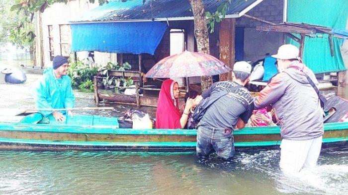 Relawan Hilal Merah Indonesia membantu mengevakuasi warga yang terjebak banjir