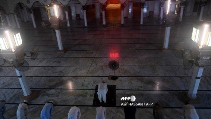 Umat ??Muslim mempertahankan jarak sosial ketika mereka menawarkan doa malam khusus 'Taraweeh' menjelang hari pertama bulan suci Ramadhan di sebuah masjid di Karachi pada 24 April 2020.