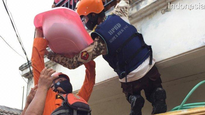 Tim rescue Basarnas dari Kantor Pencarian dan Pertolongan Jakarta melakukan evakuasi sesosok bayi korban banjir di Villa Jatirasa.