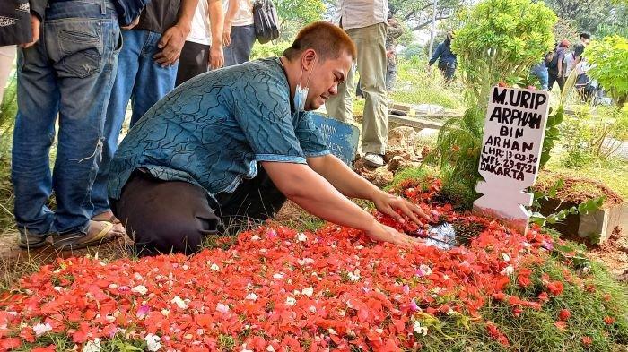 Arief menangis diatas pusara aktor Urip Arphan yang dimakamkan di TPU Kawi-Kawi, Johar Baru, Jakarta Pusat, Jumat (30/7/2021) siang. Arief adalah anak Urip Arphan.