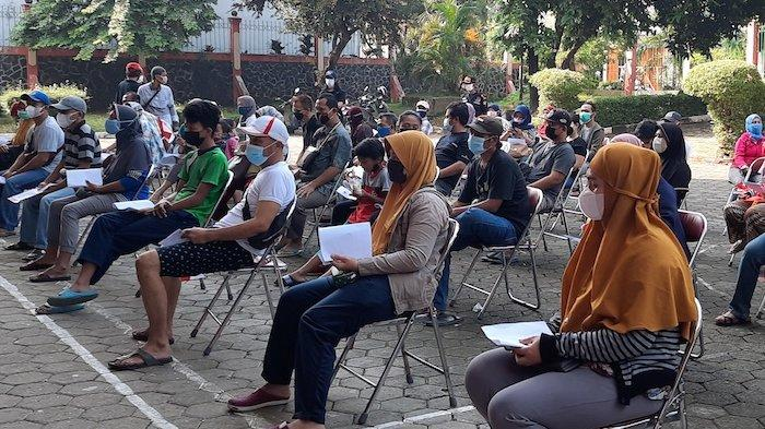 Ratusan warga Kalisari, Kelurahan Kalisari, Kecamatan Pasar Rebo, Jakarta Timur mengantre vaksinasi Covid-19 di GOR Kalisari, Minggu (1/8/2021).